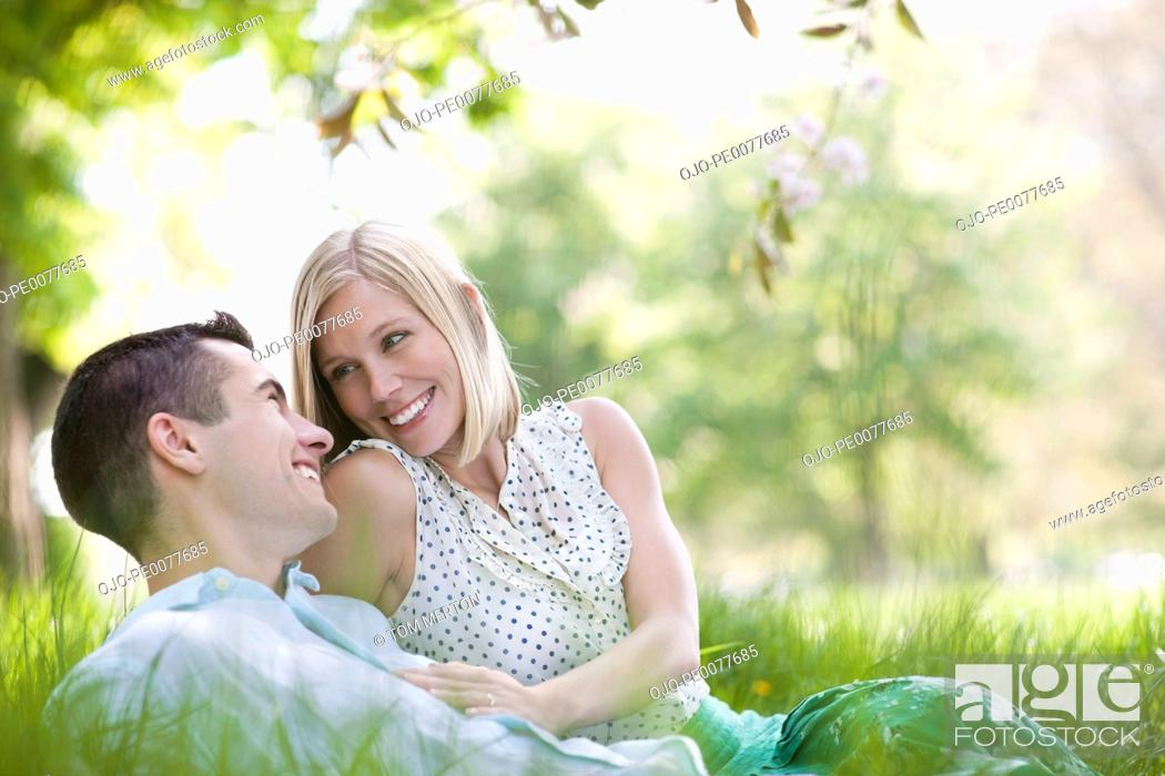 Stock Photo: Couple laying in grass together.