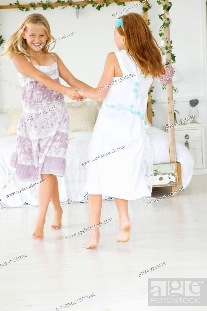 Stock Photo: Two flower girls playing in a bedroom.
