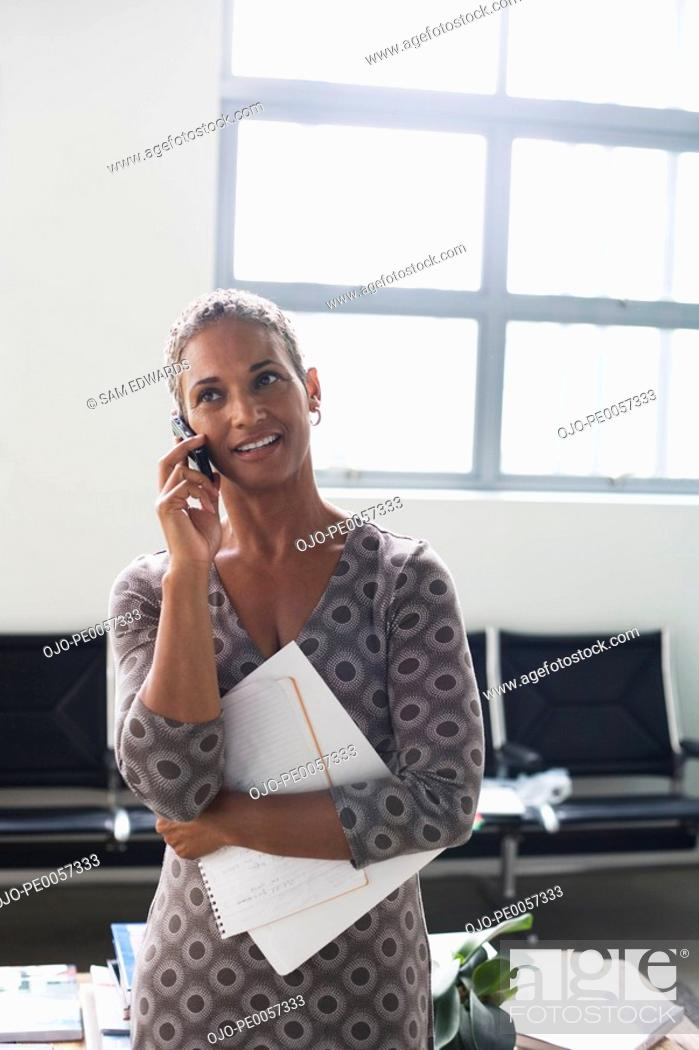 Stock Photo: Business woman on her mobile phone in office.