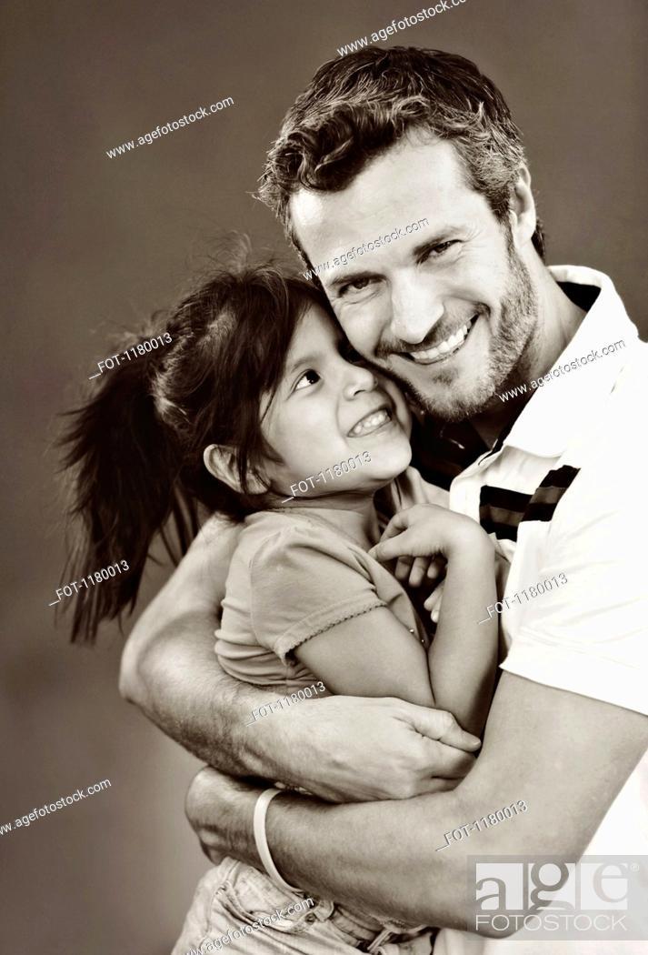 Stock Photo: A man embracing his young daughter, studio shot.