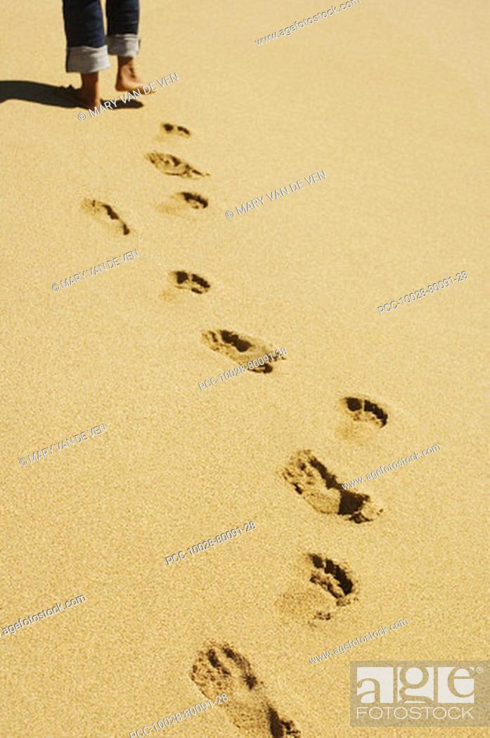 Stock Photo: Footprints in sand with legs wearing jeans and feet at top of picture.