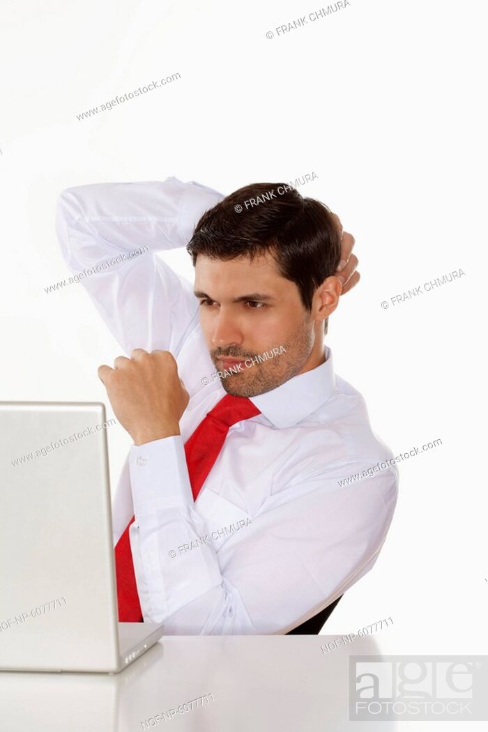 Stock Photo: Business executive in white shirt behind desk with laptop.