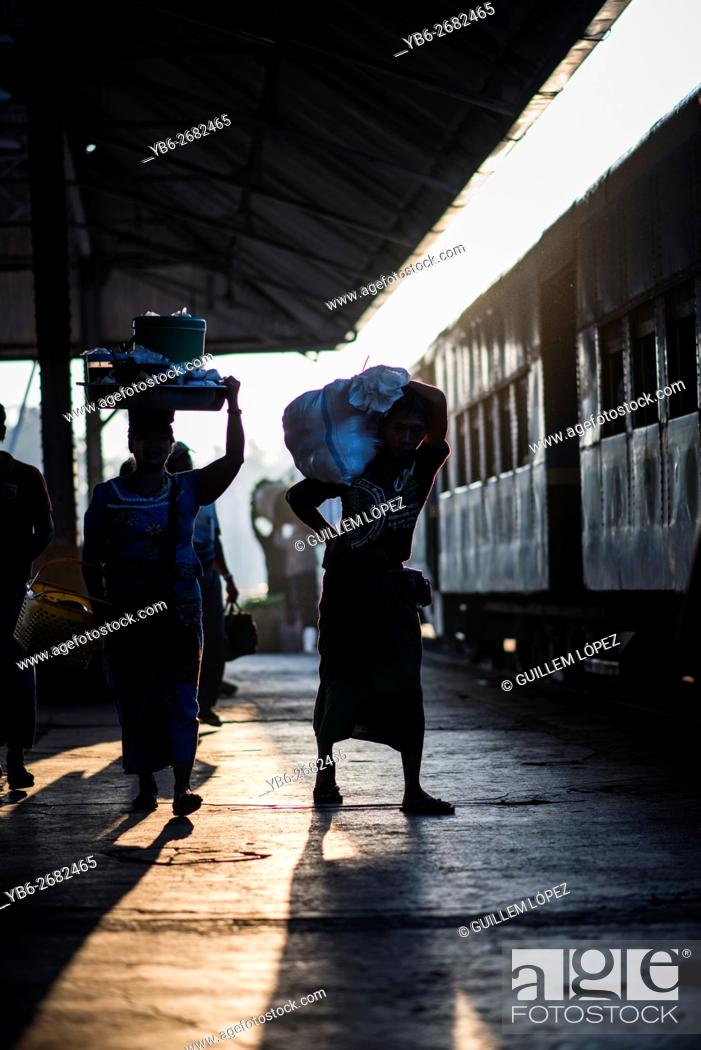 Stock Photo: Silhouette of people carrying luggage waiting for the train departure at the Yangon Central Train Station, Myanmar.