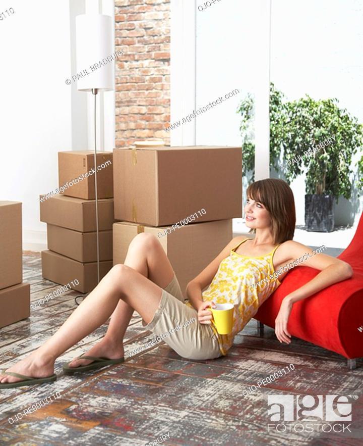 Stock Photo: Woman sitting on hardwood floor with mug and cardboard boxes smiling.