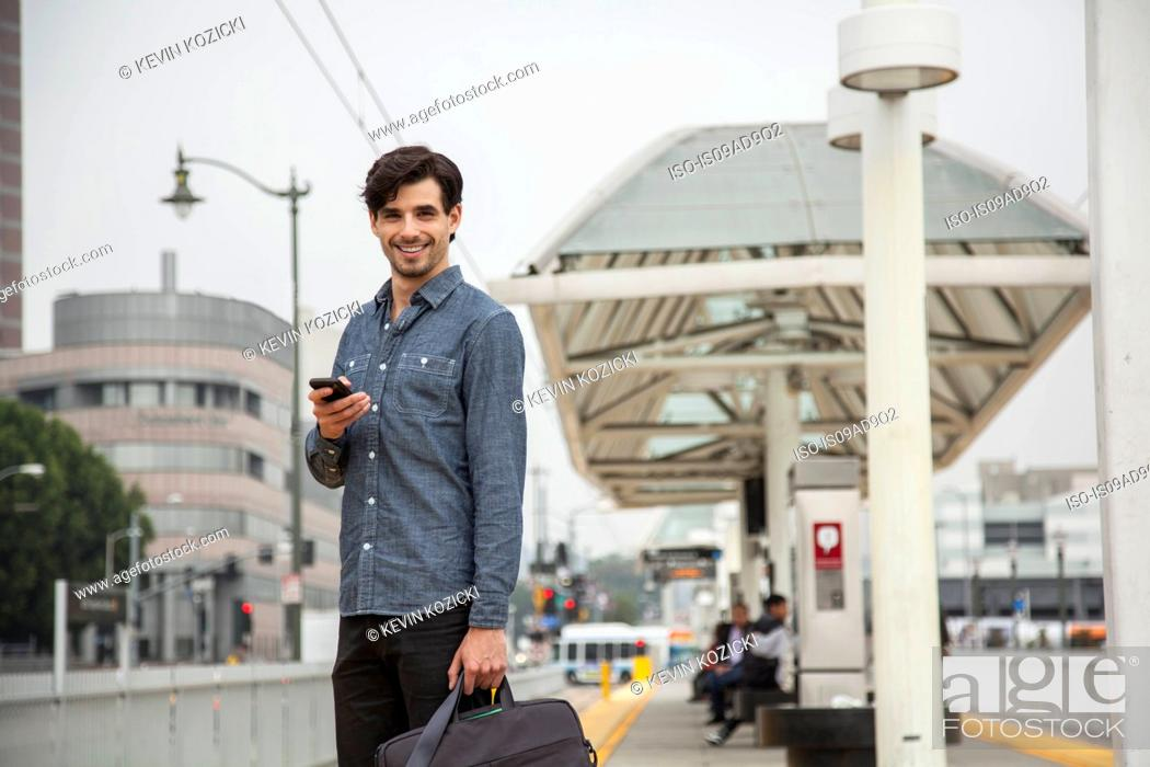 Stock Photo: Man with mobile phone at station, Los Angeles, California, USA.