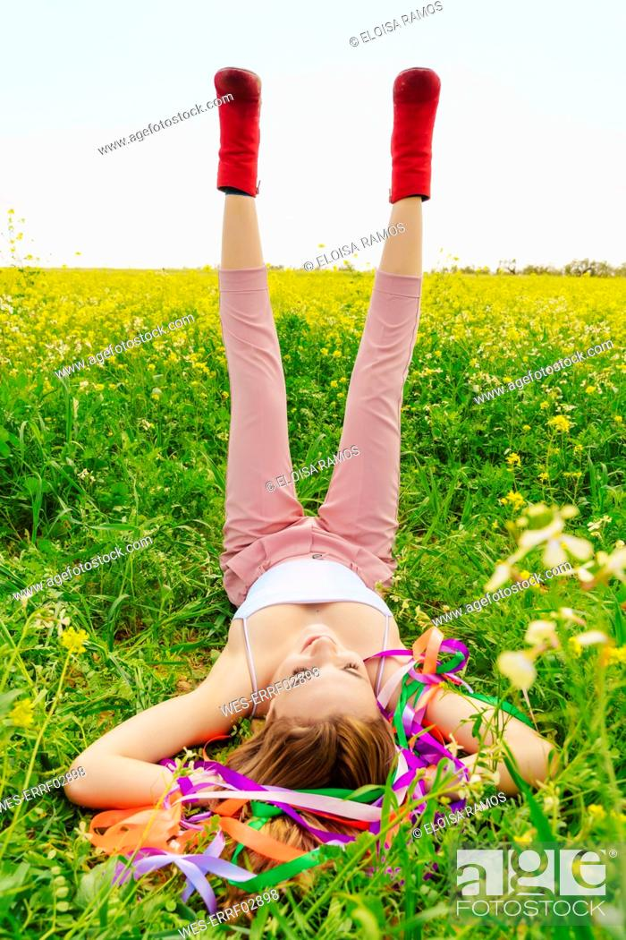 Stock Photo: Young woman wearing red ankle boots lying in a flower meadow in spring.