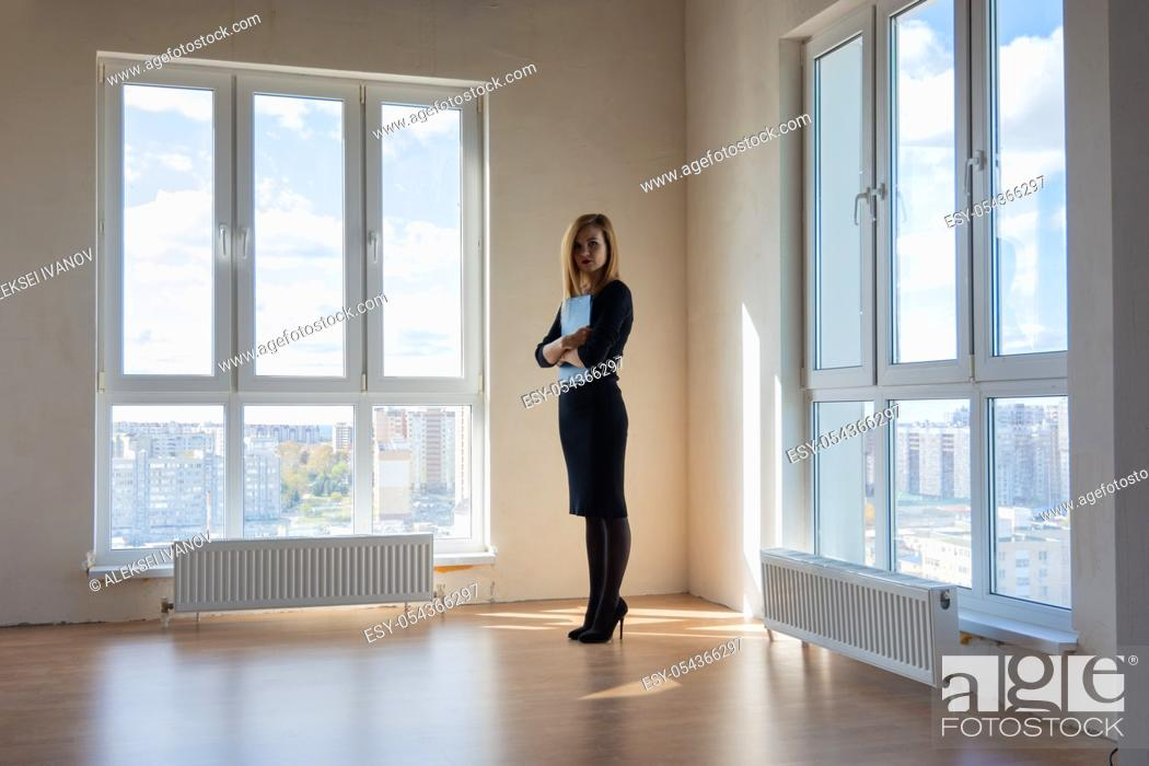 Stock Photo: Realtor expects buyers in a large room with huge windows.