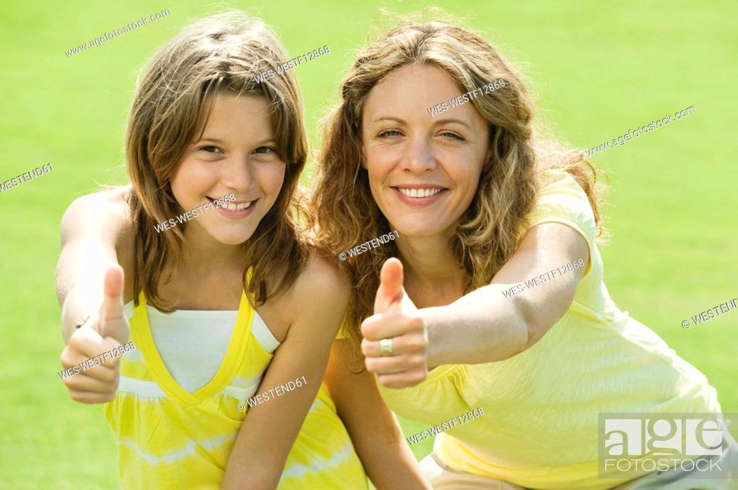 Stock Photo: Spain, Mallorca, Mother and daughter 10-11, thumbs up, smiling, portrait.
