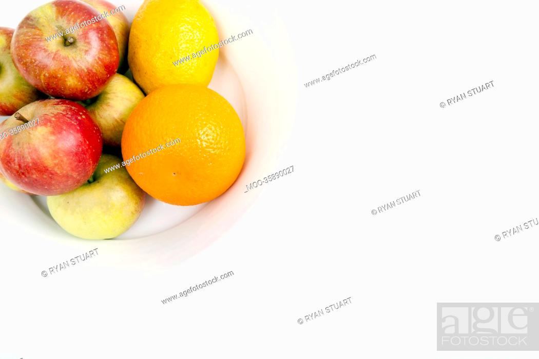 Stock Photo: Fresh apples with orange and lemon in plate against white background.