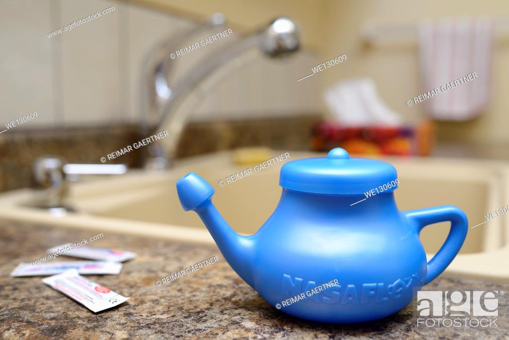 Stock Photo: Blue Neti Pot for nasal irrigation on counter by the sink with tissue box.