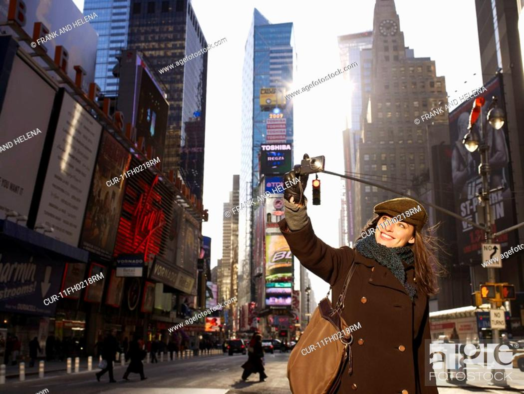 Stock Photo: Woman standing in Times Square, New York. She is smiling and taking a picture.
