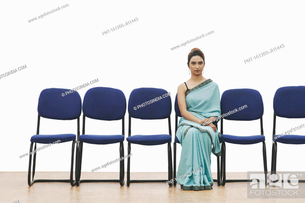 Stock Photo: Portrait of a young woman sitting on a chair.