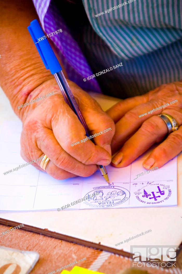 Stock Photo: Felisa, a popular person signing a credential at the begining of Logroño city along the Camino de Santiago pilgrimage way.