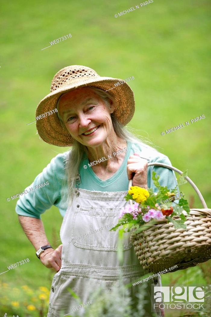 Stock Photo: Senior woman with straw hat looking into camera with basket of flowers.