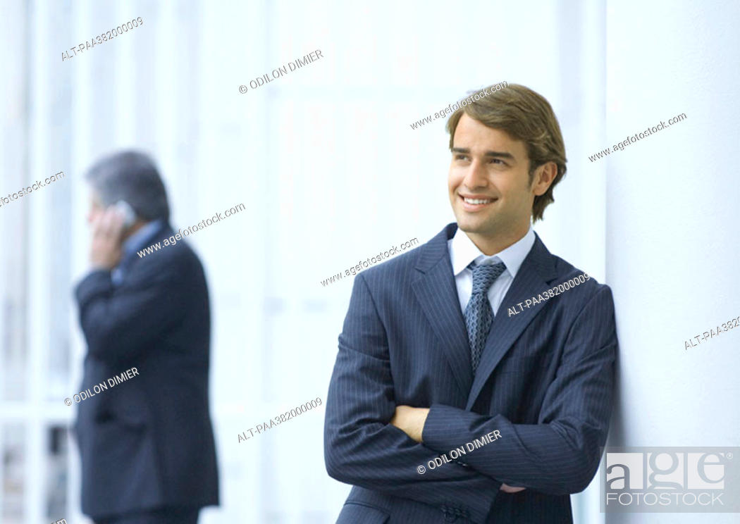 Stock Photo: Businessman leaning against column, smiling.