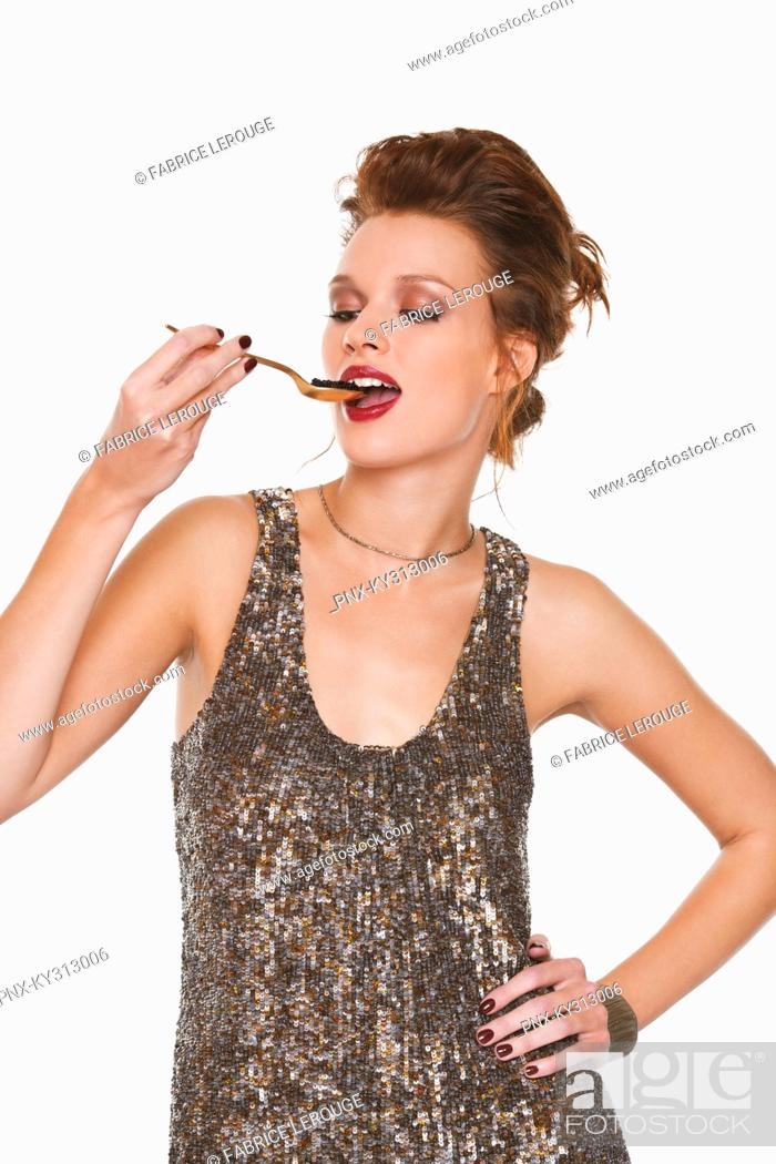 Stock Photo: Young woman eating caviar.