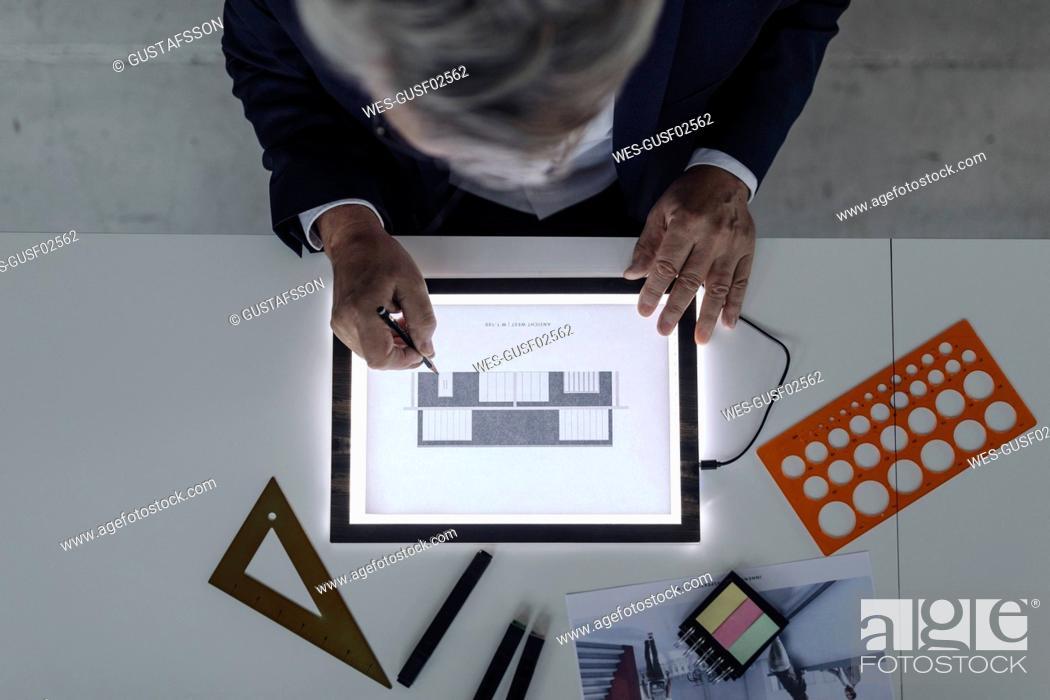 Stock Photo: Senior businessman drawing on shining tablet.