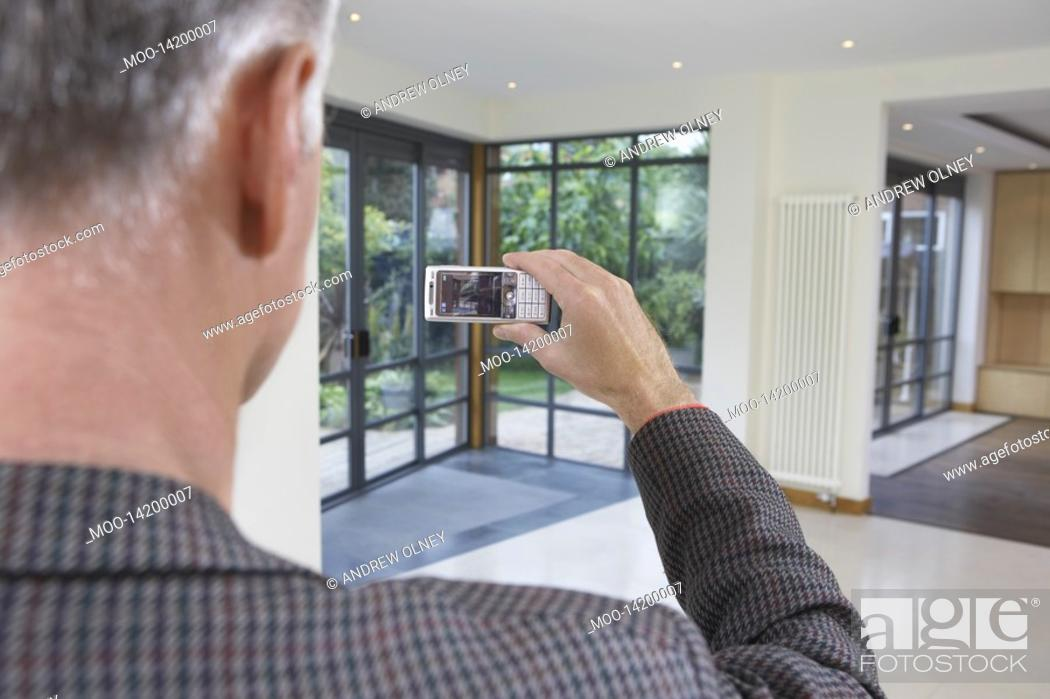Stock Photo: Real estate agent photographing new property.