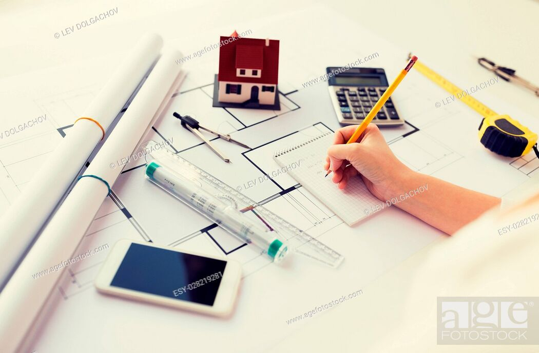 Stock Photo: business, architecture, building, construction and people concept - close up of architect hand with blueprint and architectural tools writing to notebook.