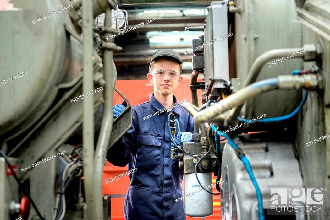 Stock Photo: Portrait of young apprentice locomotive engineer in train works.