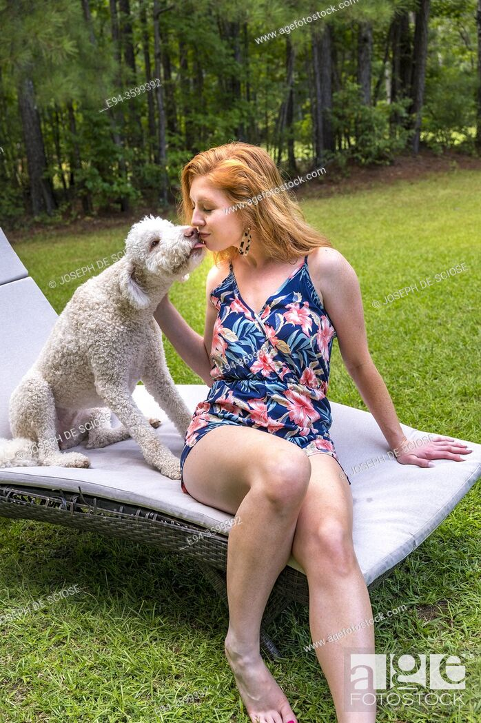 Photo de stock: A 27 year old redhead woman with her dog in the backyard.
