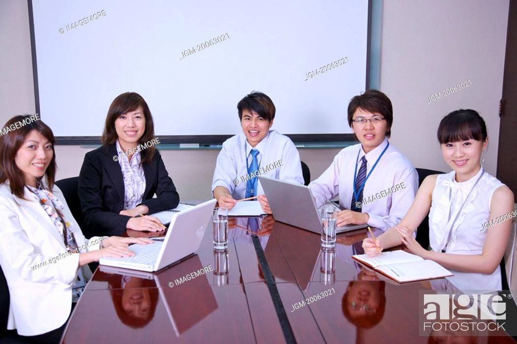 Stock Photo: Colleagues having a meeting and smiling at the camera.