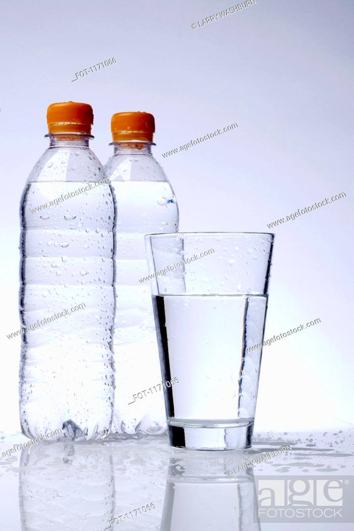 Stock Photo: Two full plastic water bottles and a drinking glass.