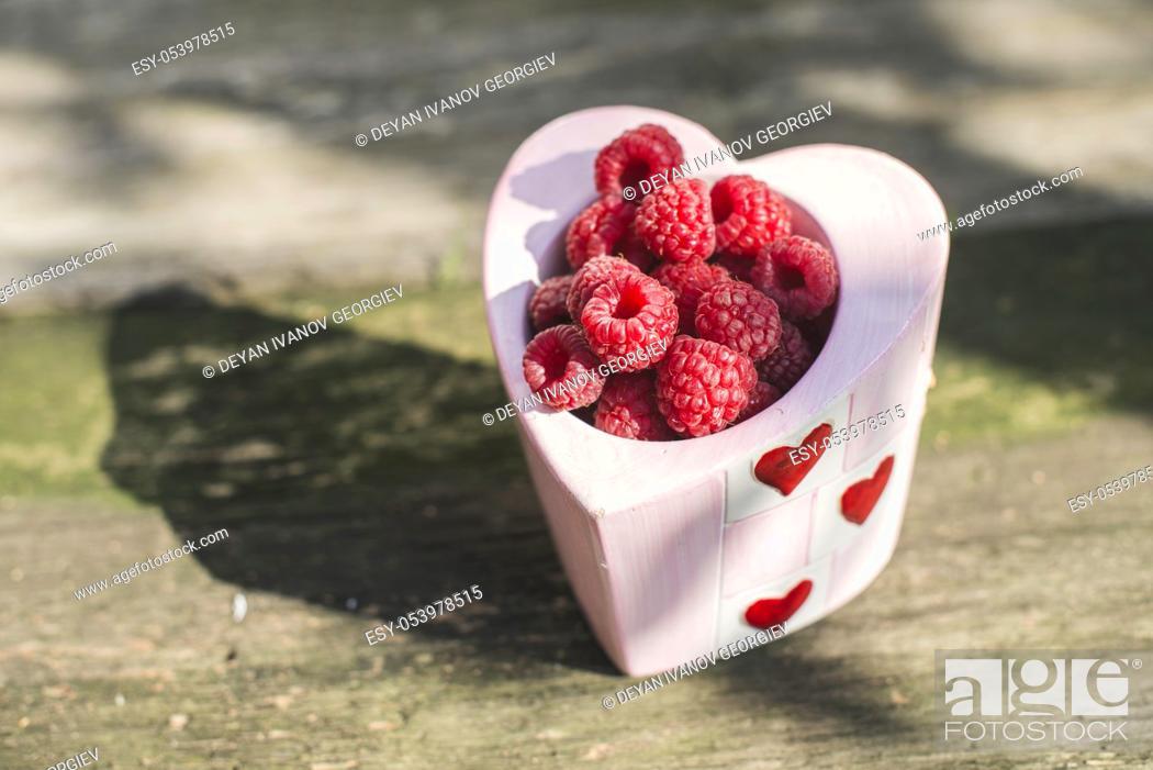Stock Photo: Raspberries in a bowl on wood. Heart shape bowl.