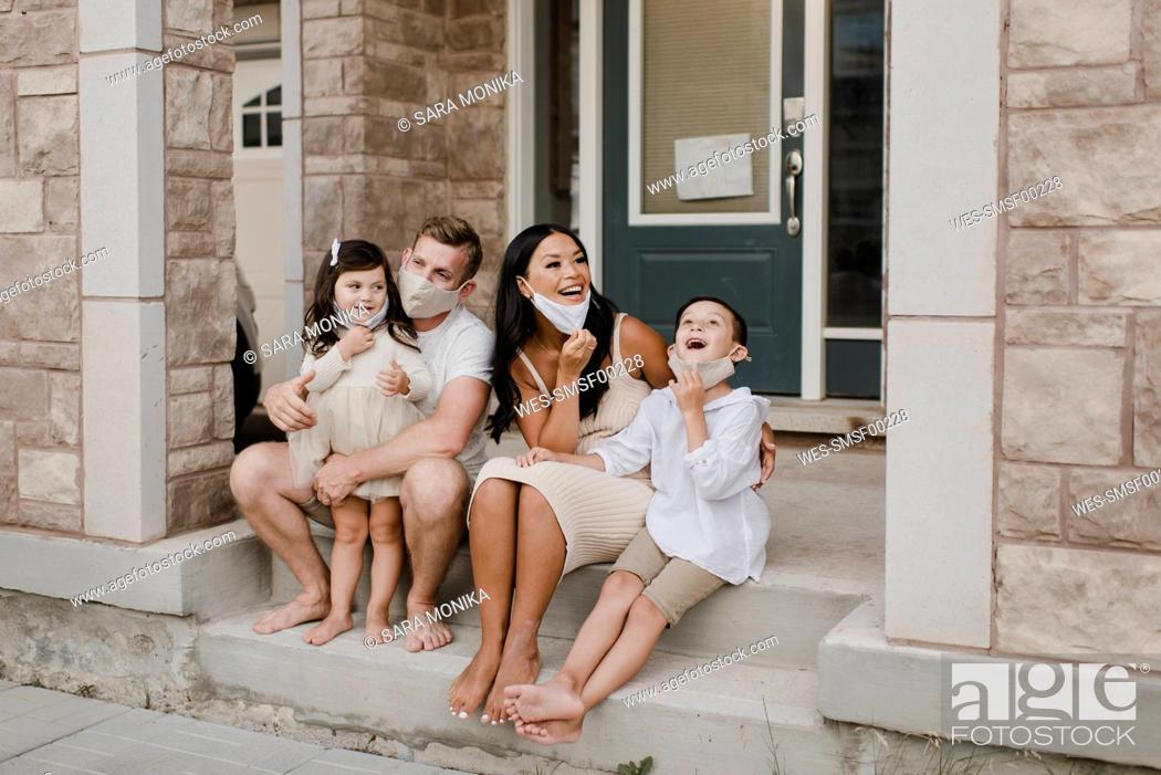 Imagen: Smiling family with kids wearing protective face mask while sitting on steps outside house.