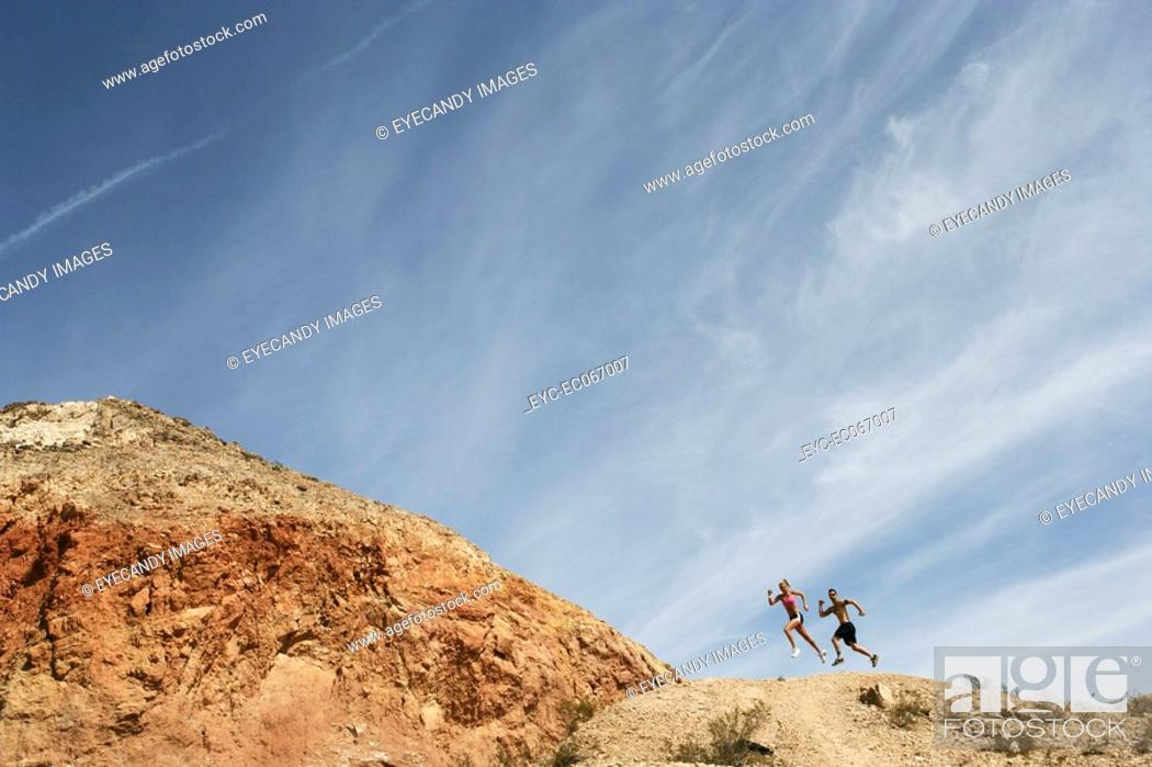 Stock Photo: People running in distance on remote terrain.