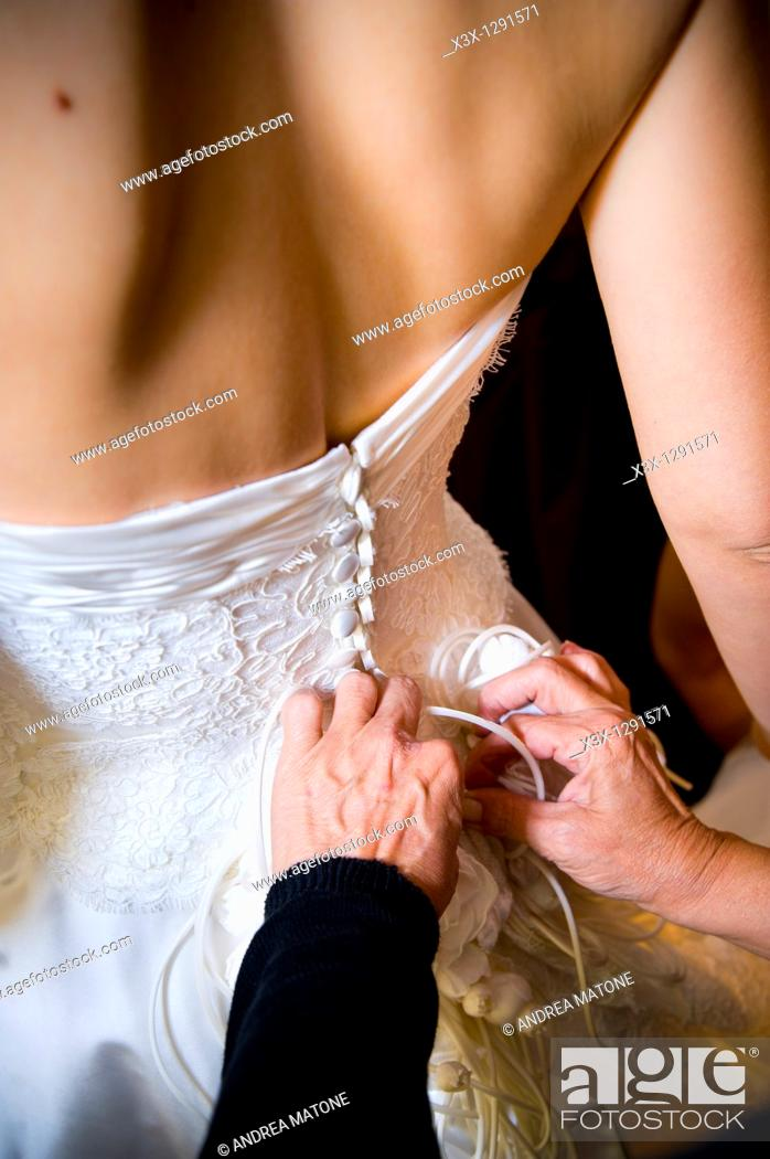 Stock Photo: Woman buttoning up the bride's wedding dress.