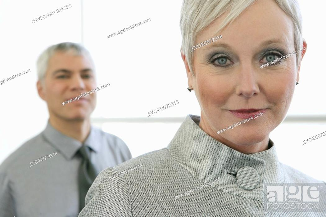 Stock Photo: Portrait of mature woman in airport with man behind.