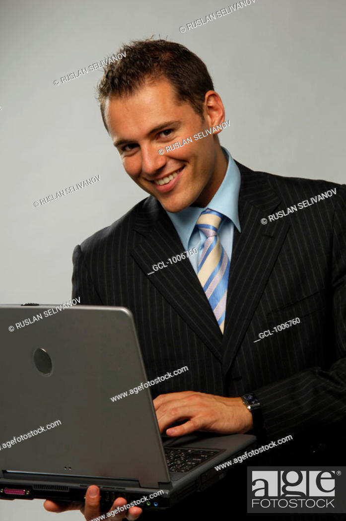 Stock Photo: Portrait of a smiling businessman with laptop.