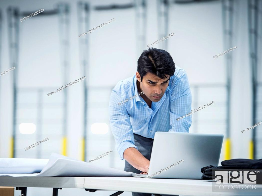 Stock Photo: Indian architect using laptop in empty warehouse.