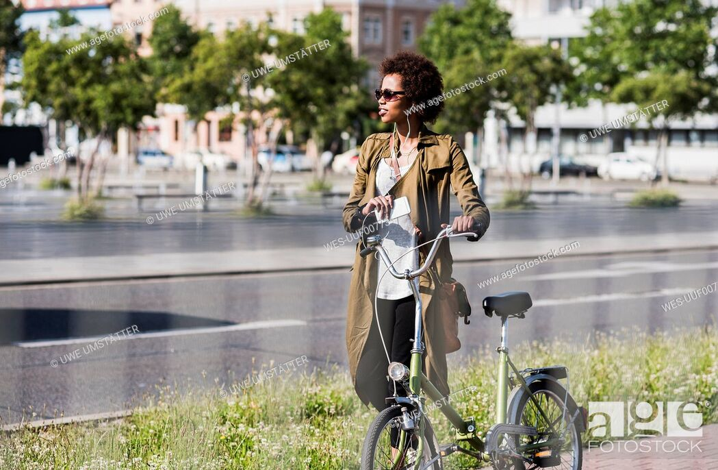 Photo de stock: Young woman with smartphone and earphones pushing bicycle.