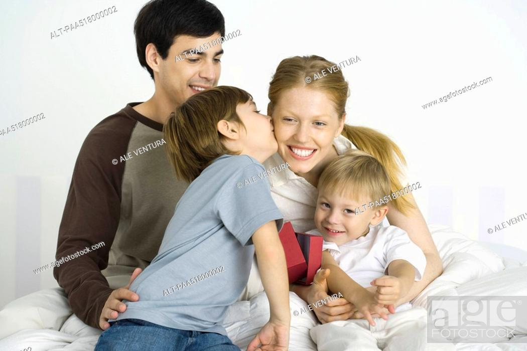 Stock Photo: Family sitting together on bed, boy kissing mother's cheek.