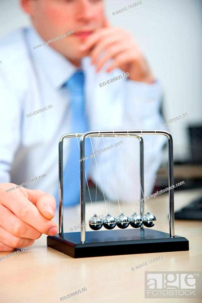 Stock Photo: Office worker playing with newtons cradle.