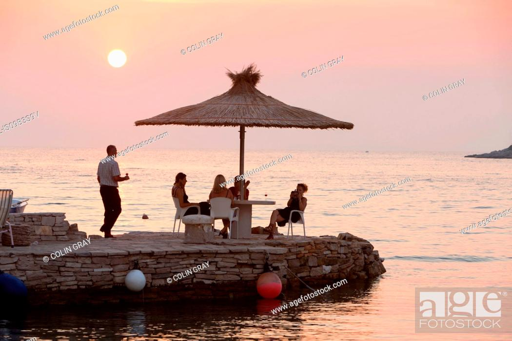 Stock Photo: Waiter serving tourists at coastal restaurant table at sunset, Loviste, Croatia.