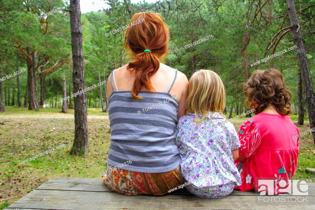 Stock Photo: mother and daughters sitting back looking nature park forest wooden bench table.