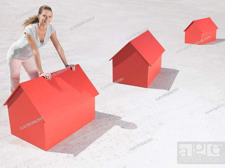 Stock Photo: Woman leaning over model houses.