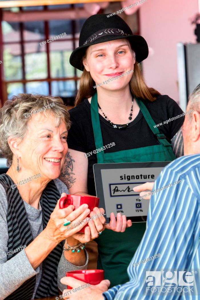 Stock Photo: Woman watching friend write signature on a tablet with finger to pay bill in coffee house.