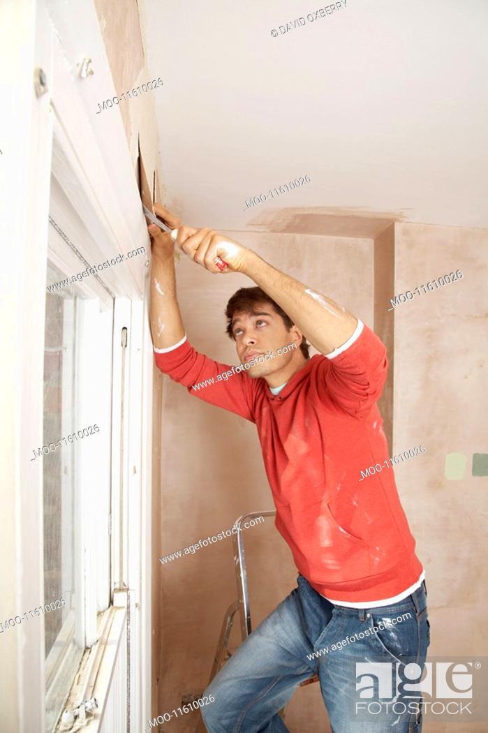 Stock Photo: Man preparing wall of unrenovated room.