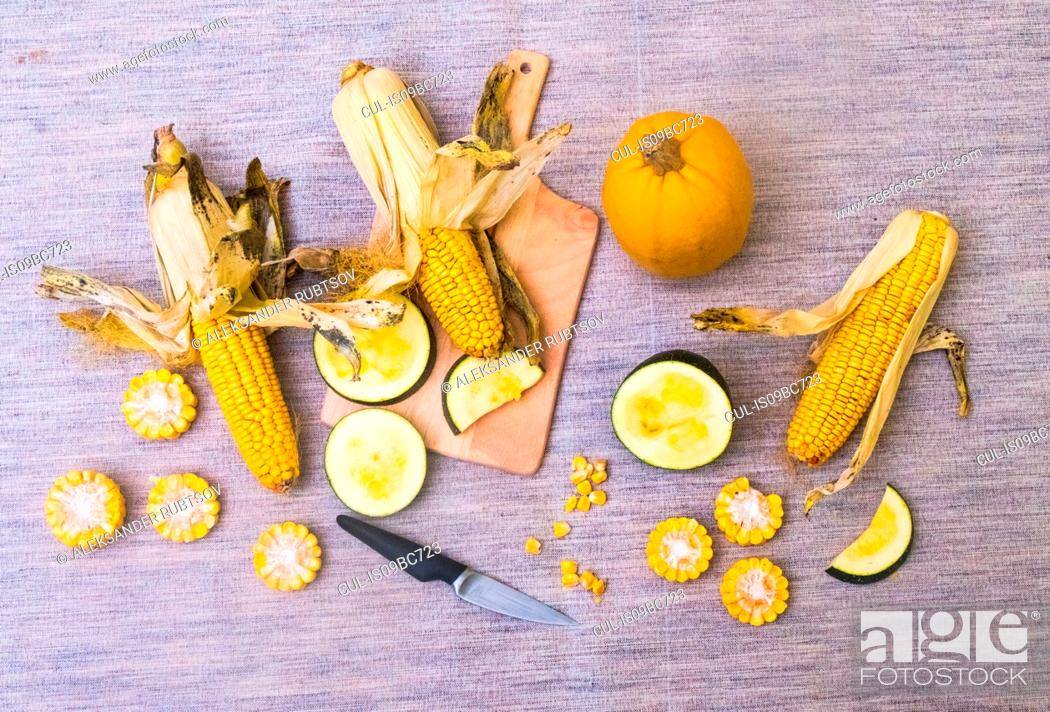 Stock Photo: Still life of corn on the cob with two varieties of squash, whole and sliced, overhead view.