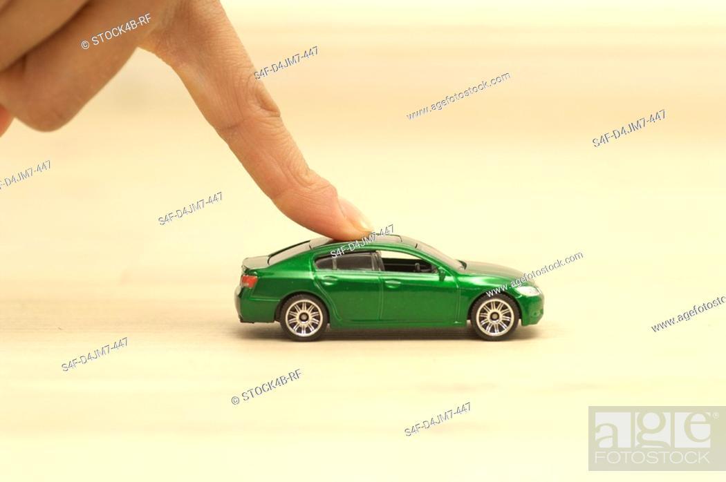 Stock Photo: Finger pushing green toy car.