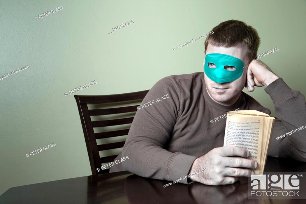 Stock Photo: Young man wearing a mask and holding a book.