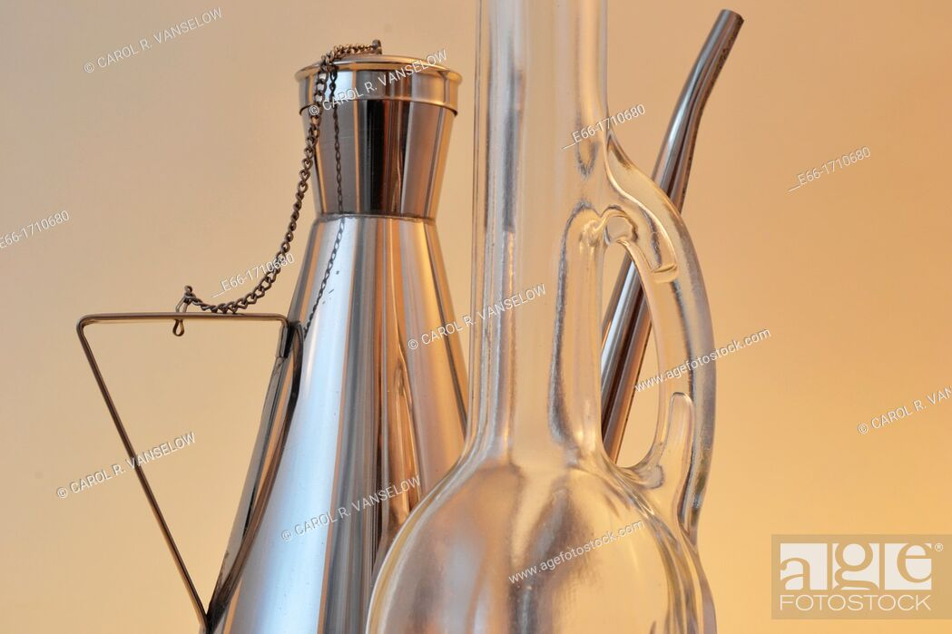 Stock Photo: two olive oil bottles: one glass with long neck, one stainless steel.