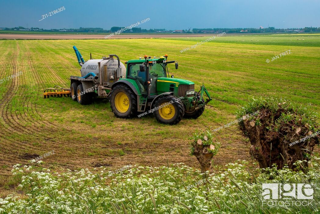 Stock Photo: tractor with manure injector at farmland in holland.