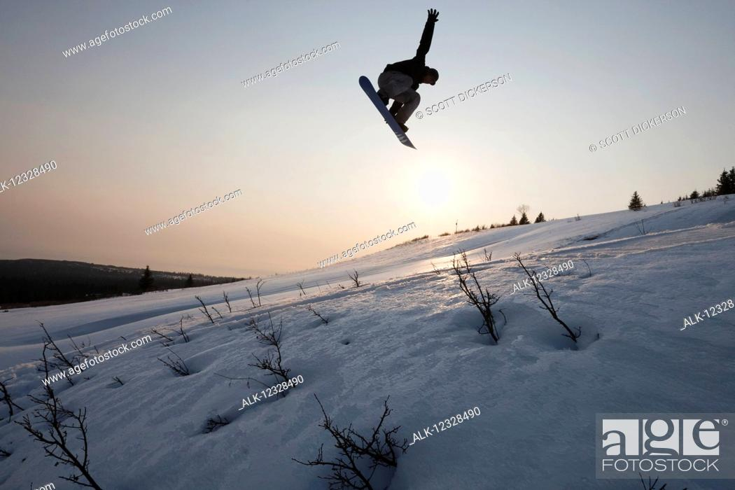 Photo de stock: Silhouette of a snowboarder in mid-jump, South-central Alaska, Homer, Alaska, United States of America.