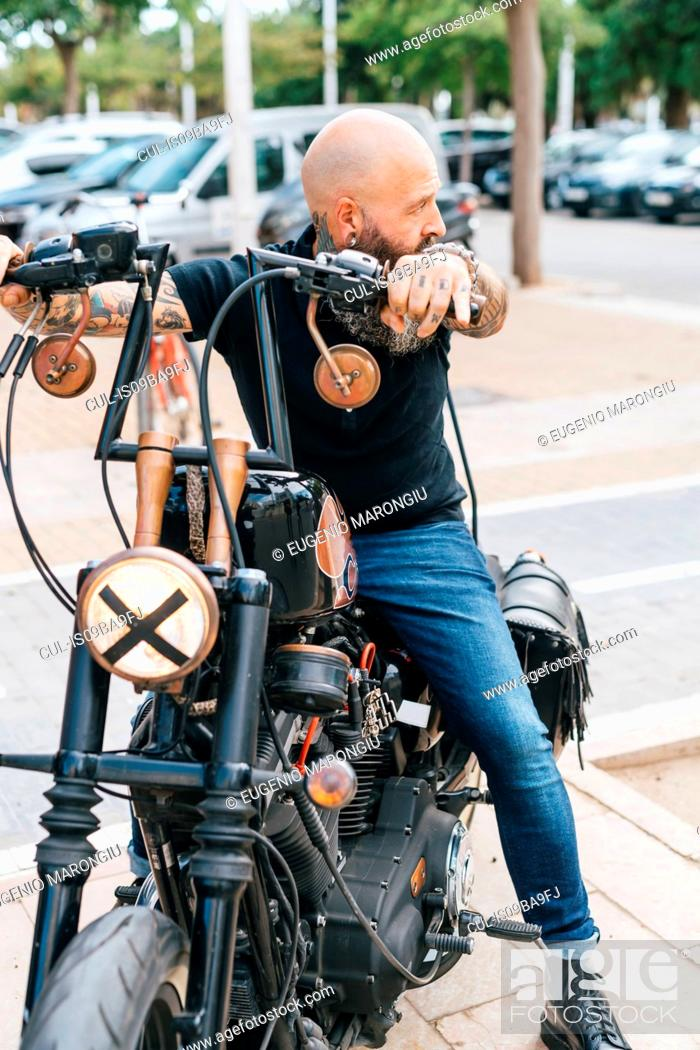Stock Photo: Mature male hipster astride motorcycle, looking over his shoulder.