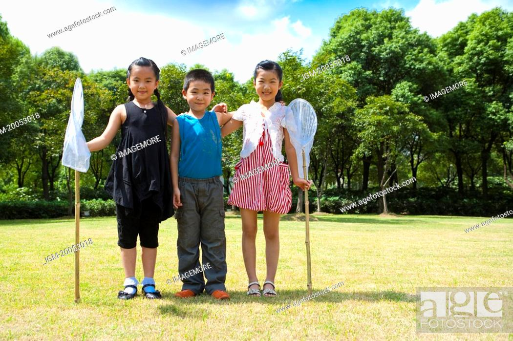 Stock Photo: Three children standing in a row and holding butterfly nets with smile.